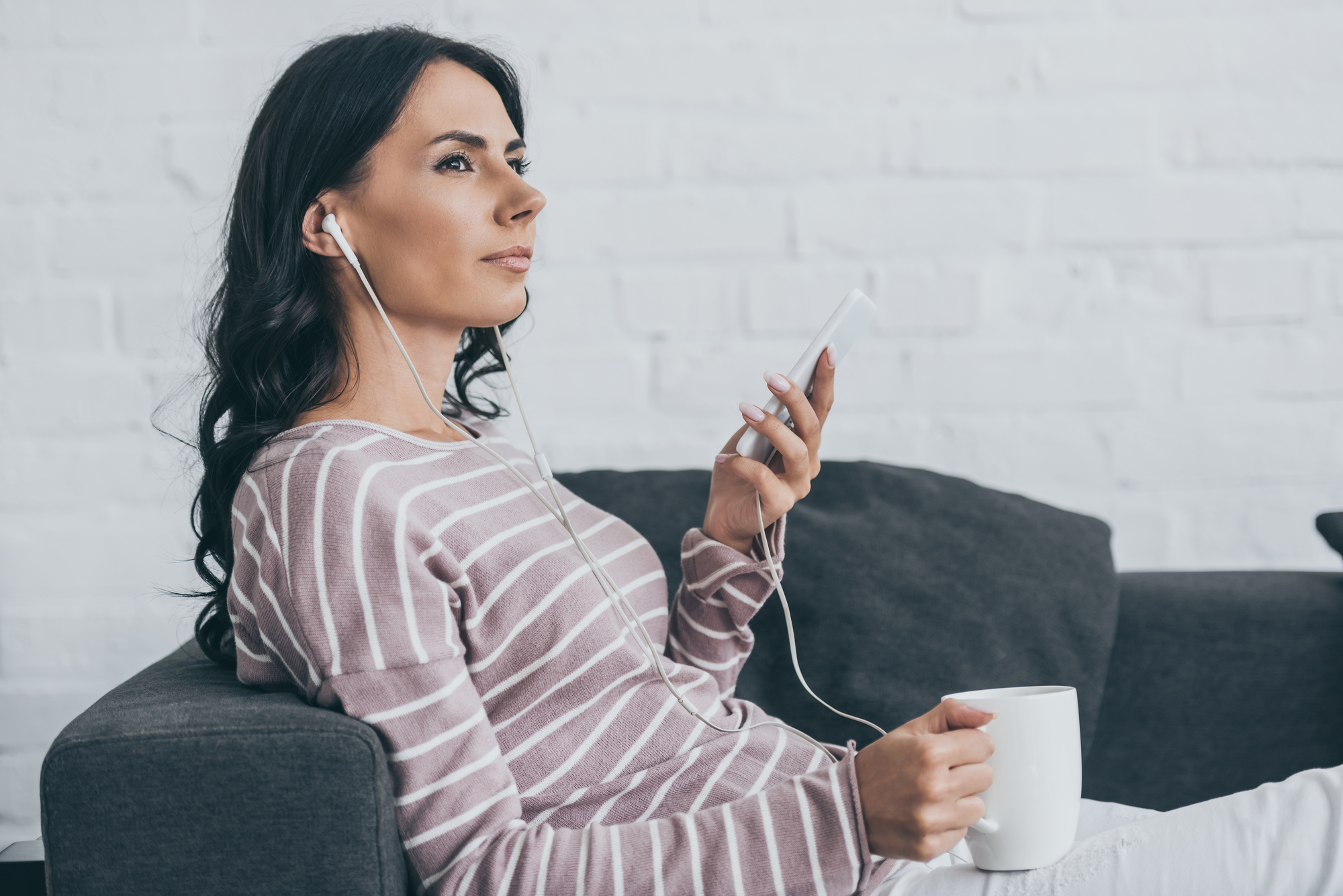 Attractive pensive woman listening music in earphones and looking away while resting on sofa