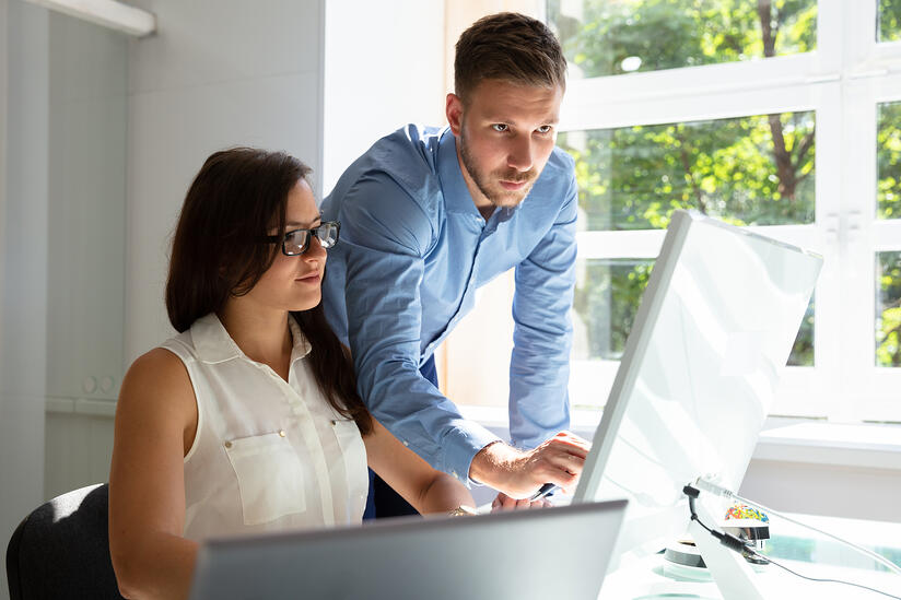 Businessman Standing Near Businesswoman Pointing At Computer Screen