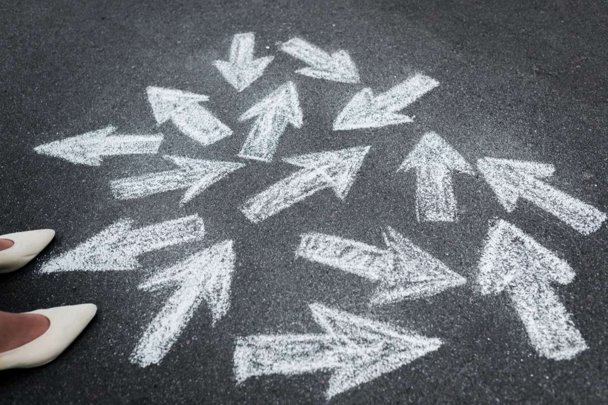Cropped view of woman standing near directional arrows on asphalt (R) (S)