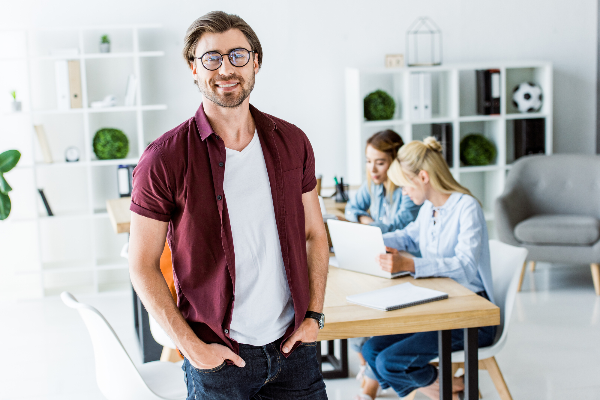 Handsome man standing in office of startup project and looking at camera