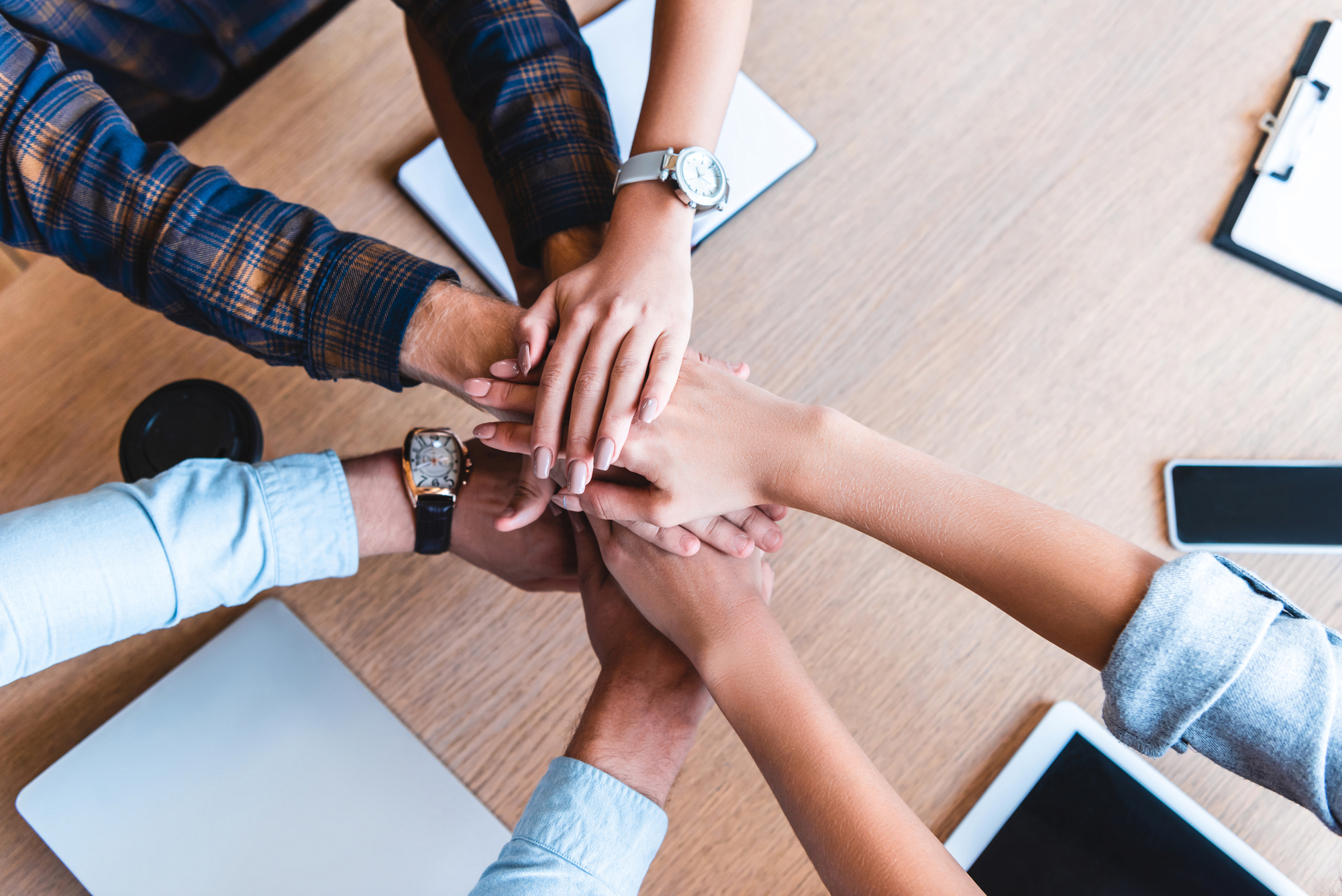 Partial top view of young business colleagues stacking hands at workplace