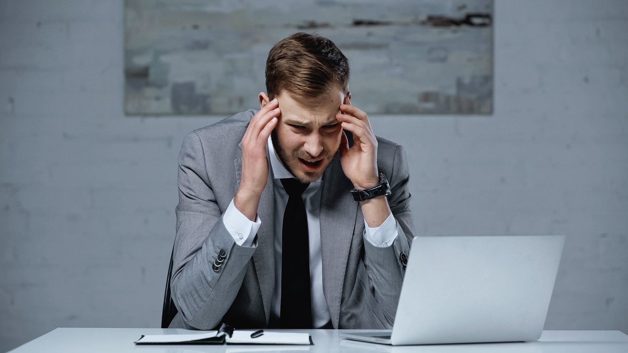 Upset businessman in suit touching head while having migraine in office